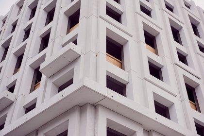 Mellan gatuvåningarnas släta fasader och dom veckade fasaderna högre upp ligger inspända balkonger som ett band runt hela byggnaden, även kallade kungsbalkonger. På Haga Nova.