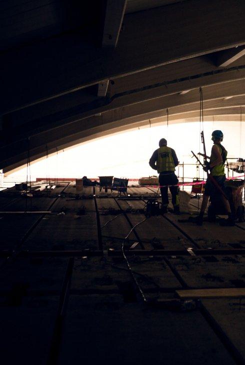 Högst upp har Strängbetongs montörer bara ett par meter till godo för att få in de flera ton tunga och flera meter långa plattorna.